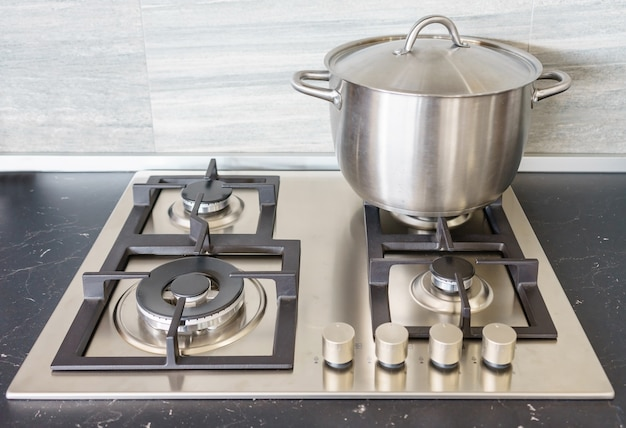 Metal pot on induction hob in modern kitchen.