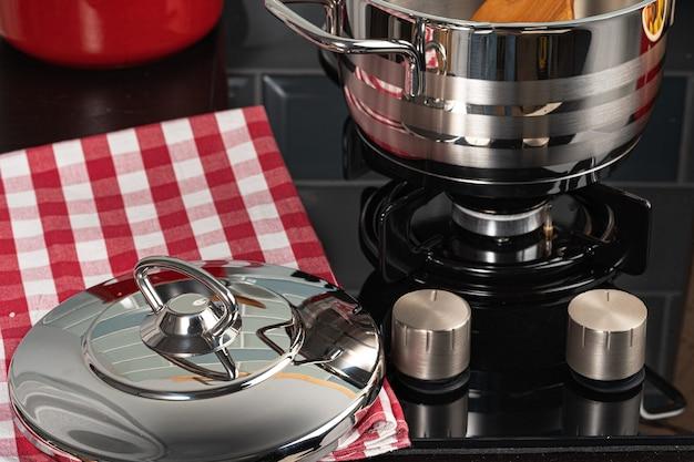 Металлический горшок на газовой плите на домашней кухне крупным планом