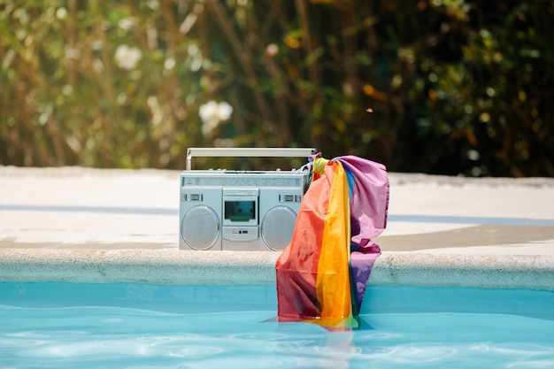 Metal radio cassette with an lgtb flag attached to the handle on a pool