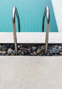 Metal rail of the ladder in a clear swimming pool