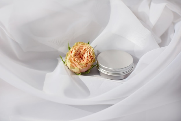Metal round jar container for eyebrow care with delicate rose on white textile scene