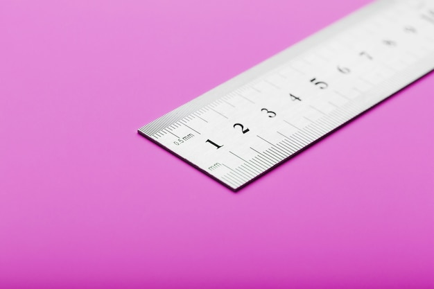 Metal ruler on pink close-up with a copy of the place for your text.