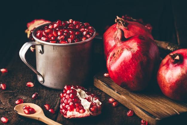 ザクロの種でいっぱいの金属製の素朴なマグカップ。暗い木の表面の全体の果物とザクロの部分。