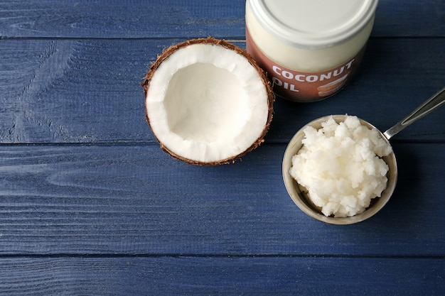 Metal scoop with fresh coconut oil taken from glass jar on wooden background