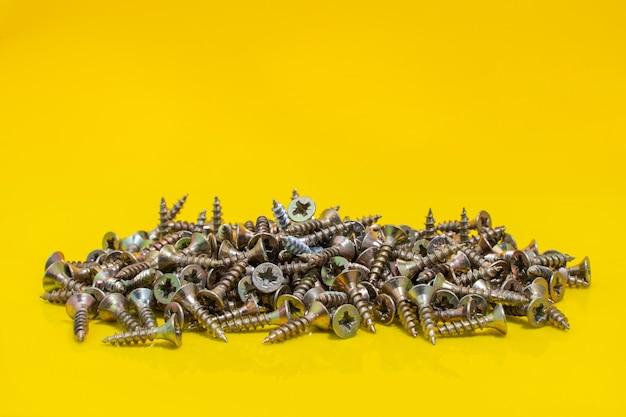 노란색 배경에 금속 나사입니다. 스톡 사진을 닫습니다.