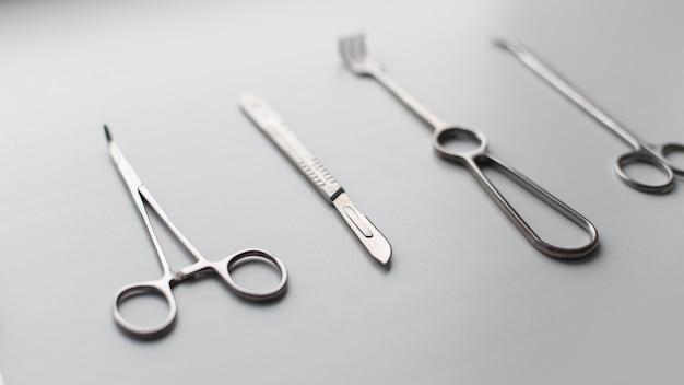 白い背景の上の医療機器の金属セット