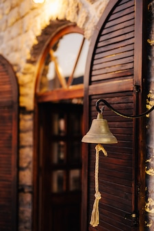 Metal ship bell hanging next to an old wooden window with shutters