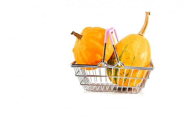 Metal shopping basket with pumpkins isolated on white.
