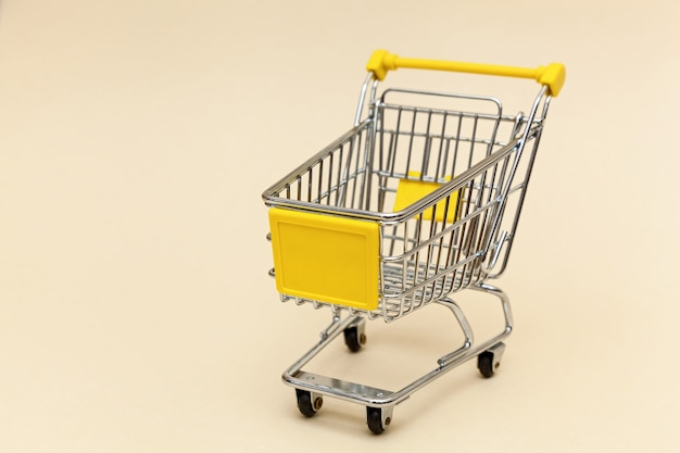 Metal shopping cart on a beige background concept objects for supermarket