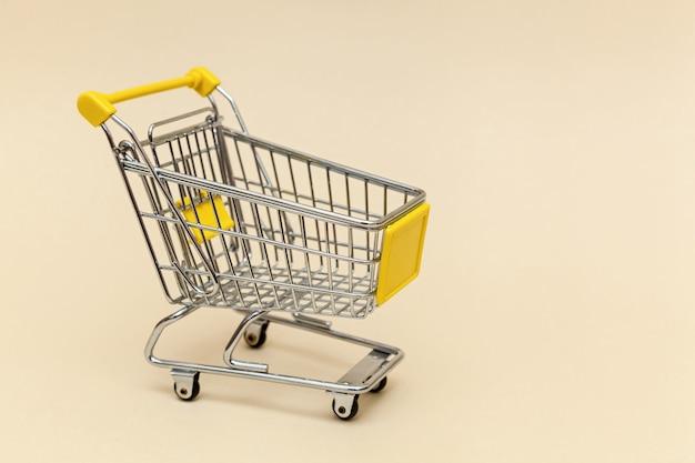 Металлическая тележка для покупок на бежевом фоне. концептуальные объекты для супермаркета. фото с местом для текста и дизайна.