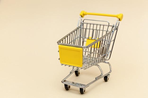 ベージュの背景に金属製のショッピングカートスーパーマーケットのコンセプトオブジェクト
