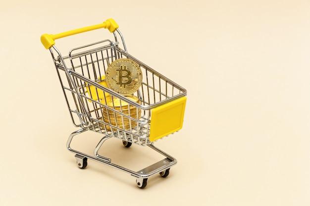 베이지색 배경에 비트코인이 있는 금속 쇼핑 카트 돈 개념