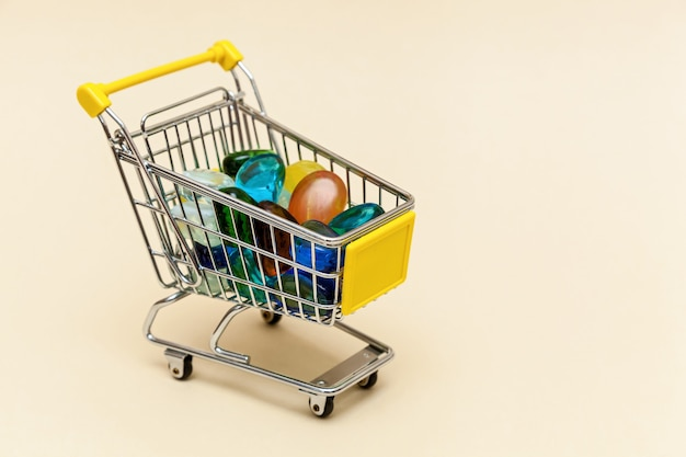 Metal shopping cart with colored stones on a beige background concept objects for supermarket