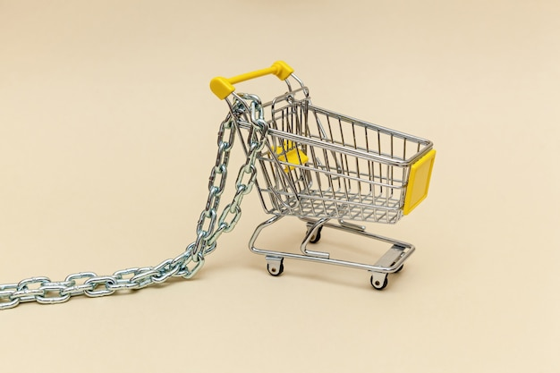 ベージュの背景に金属チェーン付きの金属製ショッピングカートスーパーマーケットのコンセプトオブジェクト