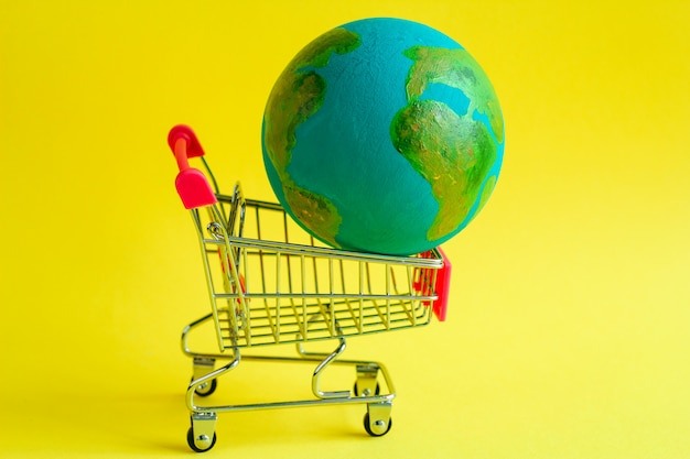 Metal shopping cart with a model of the planet earth