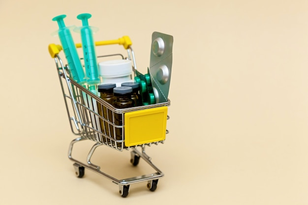 Metal shopping cart with tablets injections and syringes on a beige background