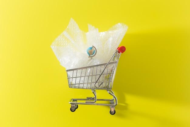 Металлическая тележка для покупок с пластиковыми отходами и землей, упакованные в полиэтиленовый пакет для кредитных карт, забота об окружающей среде. фото высокого качества