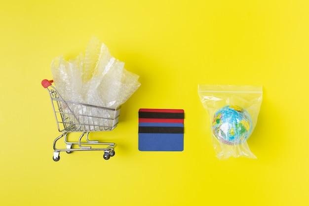 ビニール袋のクレジットカードにパッケージされたプラスチック廃棄物と土の金属ショッピングトロリー、環境への配慮。高品質の写真