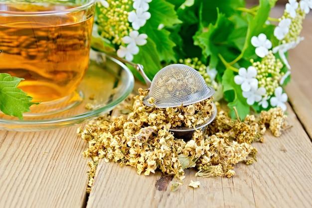 Metal sieve with dry flowers of viburnum, tea in a glass cup, fresh flowers of viburnum on a wooden boards background
