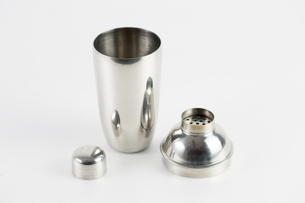 Metal silver thermos with three pieces isolated on a white wall