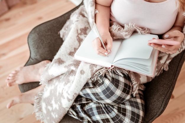 金属の滑らかなペン。居心地の良い肘掛け椅子に横たわっている間ピンクのノートに書いている白いシャツと市松模様のパジャマパンツの女性