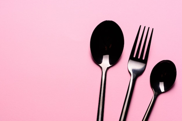 Metal spoon and fork on pink table. set of tableware ready for the meal with pink copy space