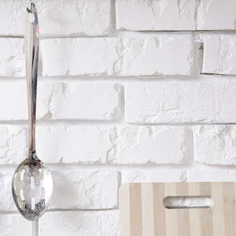 Metal spoon hanging on white brick wall