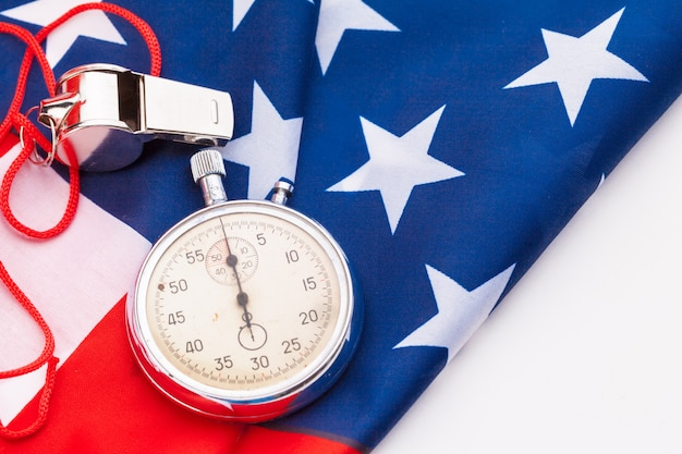 Metal sport whistle and stopwatch on american flag