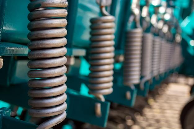 Металлические пружины, стоящие в ряд на почвообрабатывающем агрегате