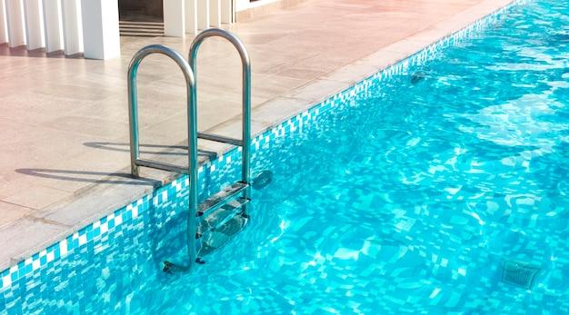 수영장용 금속 계단. 큰 집, 호텔의 수영장. 복사 공간