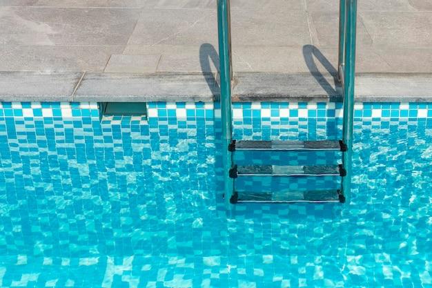 수영장에서 금속 계단입니다. 큰 집, 호텔의 수영장에서 푸른 물. 복사 공간