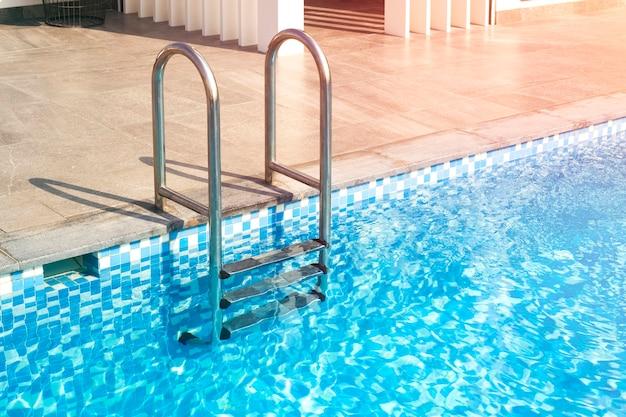 금속 계단은 수영장으로 연결됩니다. 큰 집의 수영장에 있는 푸른 물