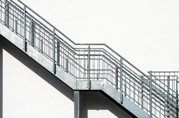 白い建物の壁に金属製の階段