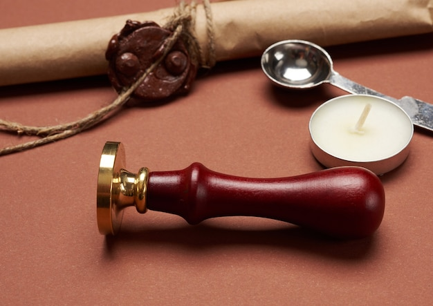 Metal stamp on wooden handle for sealing envelope, candle and brown paper roll, brown background