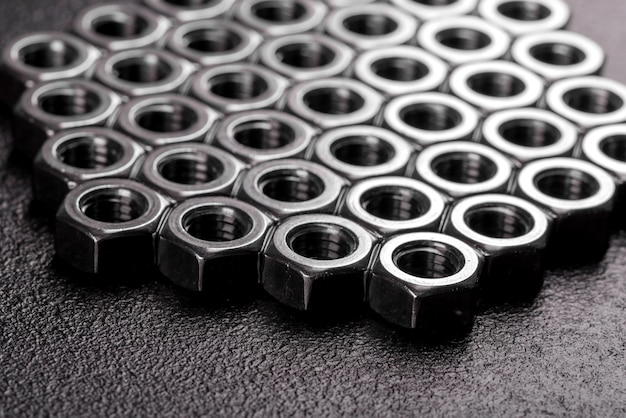 Metal steel nuts laid in composition on a dark table