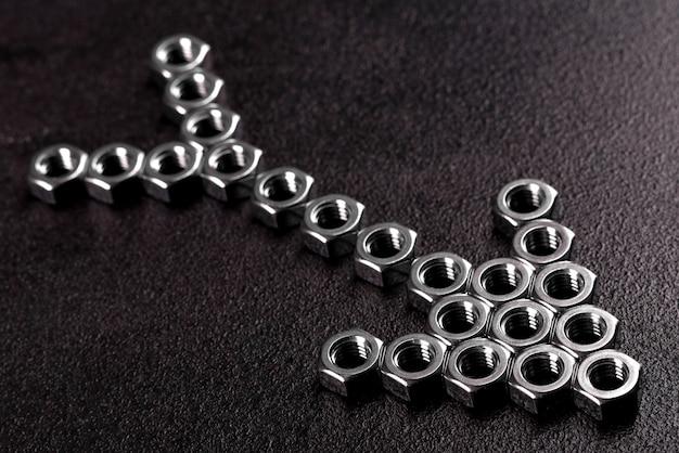 Металлические стальные гайки уложены в композицию на темный стол