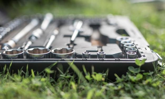 Metal steel repair tools in box on green grass closeup
