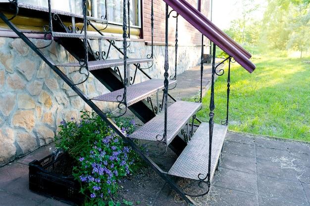 여름 봄에 잔디와 금속 강철 계단 사다리 계단 벽돌 집 정원 뒤뜰