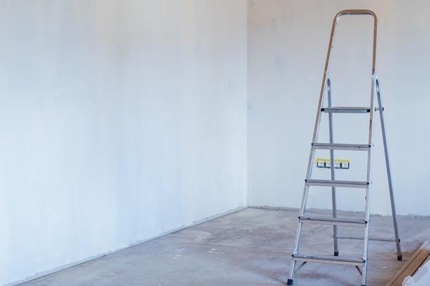 コンクリートの床と漆喰の壁のある部屋の金属製脚立。家の改修と改善