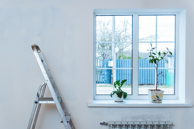窓の近くに漆喰の壁がある部屋の金属脚立。家の改修と改善