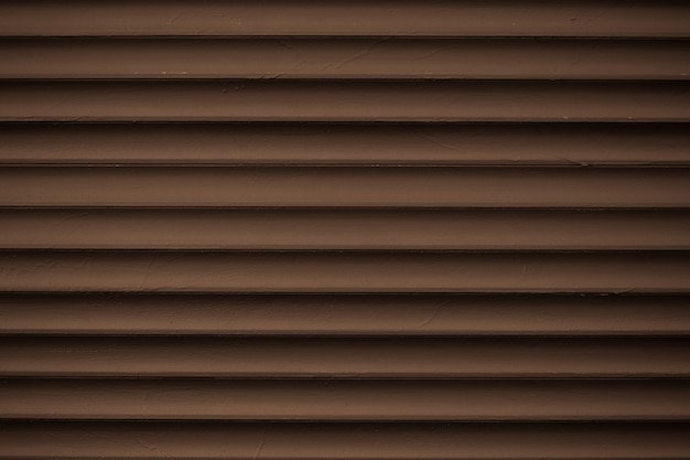 Metal striped pattern. dark brown ribbed siding texture. lines of fence, abstract grooved background.