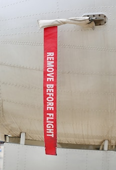 Metal surface of military aircraft with red ribbon warning caution