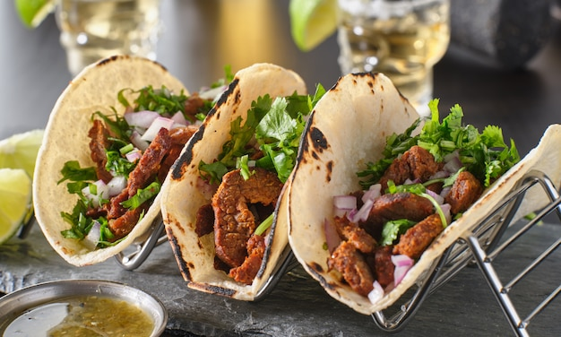 Metal taco holder with three mexican carne asada street-tacos