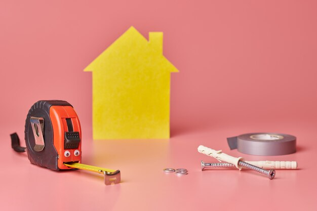 Metal tape measure funny concept. house renovation. home repair and redecorated concept. yellow house shaped figure on pink .