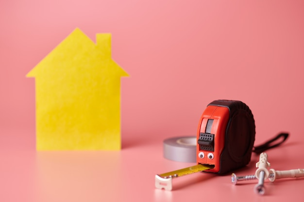 Metal tape measure and other repair items with yellow house