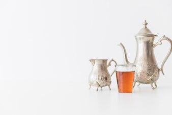 Metal tea set and glass of tea