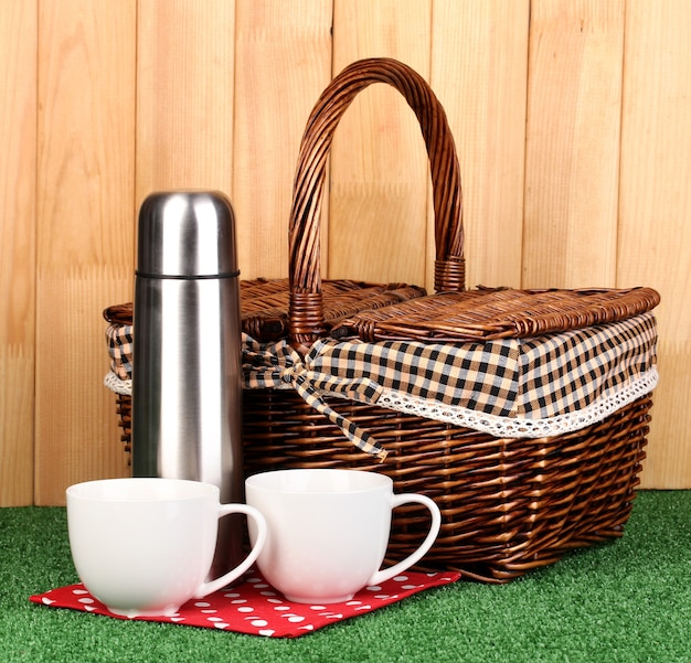 Metal thermos with cups and basket on grass on wooden surface