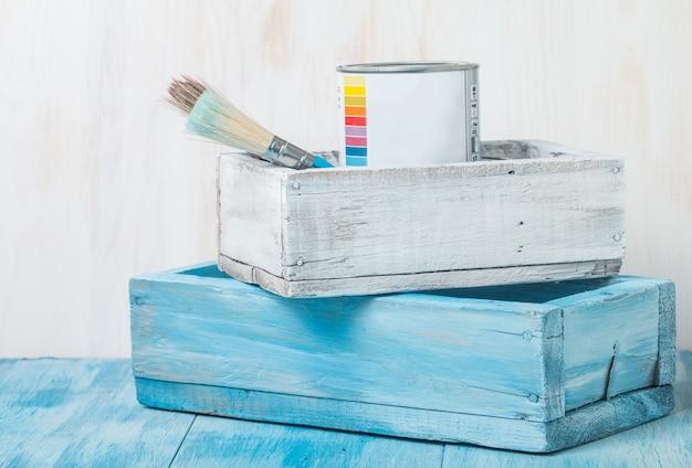 나무 상자에 페인트와 브러시가있는 금속 주석 캔