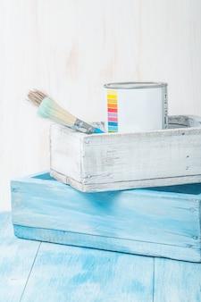 Жестяная банка металлическая с краской и кистью в деревянном ящике
