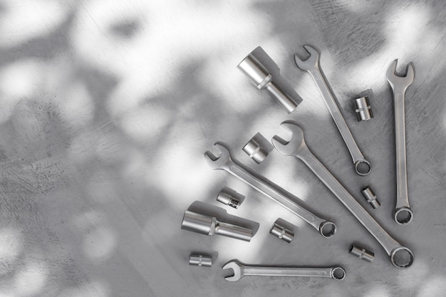 Metal tools on gray concrete floor with abstract shadow from tree leaves onstruction background